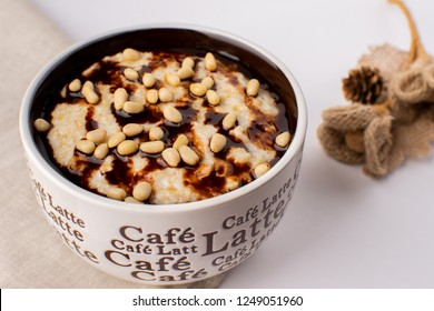Oatmeal with chocolate syrup and pine nuts