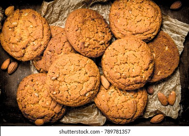 Oatmeal cookies with almonds. On a rustic background.