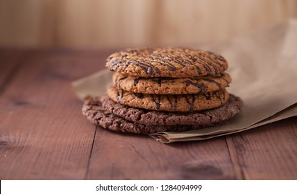 oatmeal cookies with chocolate on a brown paper on a wooden table. Cookies with chocolate lie on a wooden table