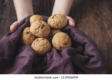 oatmeal cookies with chocolate on a wooden table