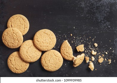 Oatmeal cookies and crumbs on old black metal background, top view