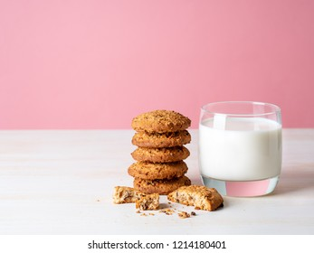 Oatmeal cookies with flax seeds and milk in a glass, healthy snack. Light background, bright pink wall