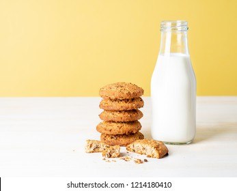 Oatmeal cookies with flax seeds and milk in bottle, healthy snack. Light background, bright yellow wall