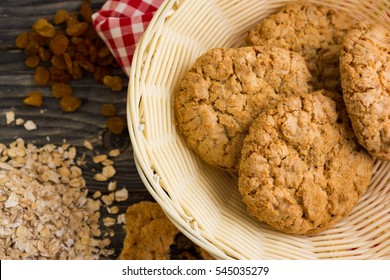 Oatmeal cookies and ingredients on a wooden table in rustic style
