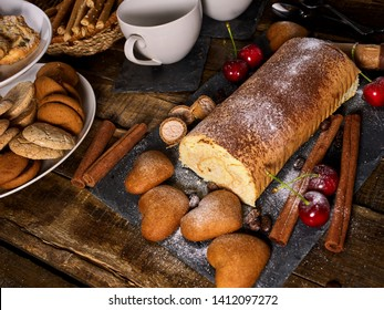 Oatmeal cookies and rolled cake on tier cake stand with cherry and nut on kitchen on wooden table in village style. Two cups of tea on wooden table. Delight pleasant taste. Useful for digestion.