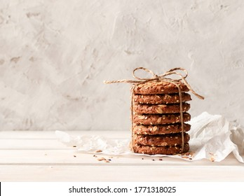 Oatmeal cookies with seeds and cereals. A stack of oatmeal cookies tied with string on white paper on a light background with space for text.