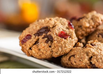 Oatmeal cranberry chocolate cookies with warm fall colors in the background.