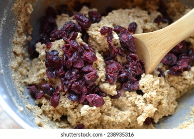 Oatmeal cranberry raisin cookie dough being stirred in a mixing bowl