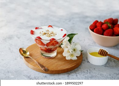 Oatmeal dessert with fresh strawberries. Healthy breakfast of strawberry parfait with fresh fruit and yogurt on a gray table. Panna Cotta. Correct, natural nutrition. Space for text. Still life