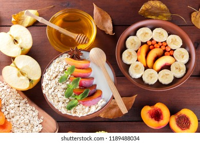 Oatmeal with different fruits and honey. Oat flakes with milk and dried apricots on wooden background. Healthy food for vegan. Dry oats with berries of mountain ash and green mint. Autumn pattern