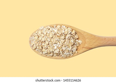 Oatmeal flakes in a big wooden spoon isolated on a  light yellow background, diet product, natural color, high contrast.
