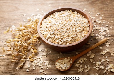 oatmeal flakes and ears of oat on wooden table