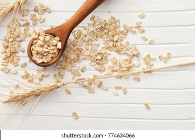 Oatmeal flakes and spoon on wooden background