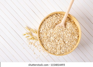 Oatmeal flakes in a wooden bowl on a white background. A wooden spoon in a bowl with porridge.