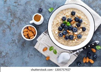 Oatmeal with fresh raw blueberry, almond nuts and honey for breakfast. Healthy vegetarian food. Top view