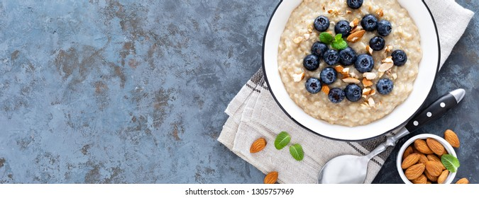 Oatmeal with fresh raw blueberry, almond nuts and honey for breakfast. Healthy vegetarian food. Top view. Banner