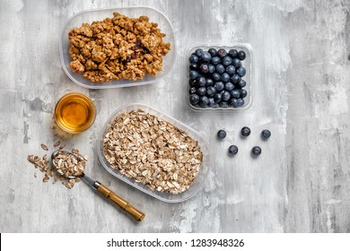 Oatmeal with granola, blueberries and sweet honey on grey background