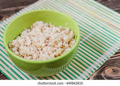 Oatmeal in Green Bowl on Wooden Table