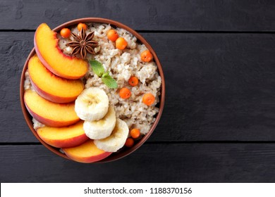Oatmeal and honey on dark wooden boards. Cooked oatmeal with fruit and honey for breakfast. Healthy food in earthenware. Peaches, bananas, mint and mountain ash with porridge