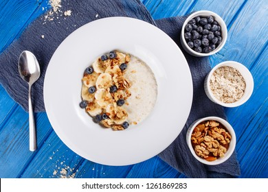 Oatmeal Muesli Blueberry and Banana Top Down View. Porridge Bowl with Walnut and Berry Ingridient Healthy Food Breakfast on Wooden Blue Background. Cereal Flakes of Milk or Yogurt in White Plate