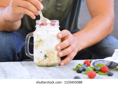 Oatmeal and muesli with yoghurt, blueberries and raspberries for breakfast - Healthy food - Close-up of a man eating breakfast