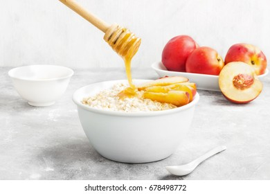 Oatmeal with nectarine and honey on a gray background