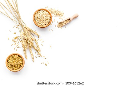 Oatmeal and oat in bowls near sprigs of wheat on white background top view copy space
