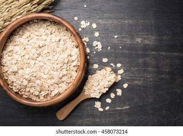 Oatmeal or oat flakes on dark wooden table