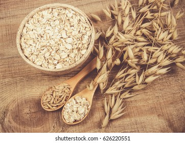 Oatmeal and oatmeal on the wooden background. Healthy eating concept.