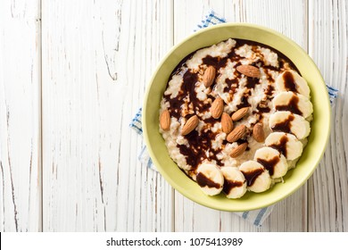 Oatmeal porridge with banana, almonds and chocolate syrup on white wooden background. Top view. Copy space.