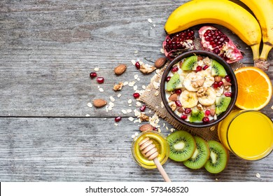 oatmeal porridge with banana, kiwi fruit, pomegranate, nuts and honey in a bowl with egg and fresh orange juice for healthy breakfast on rustic wooden background. top view