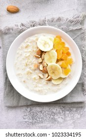 Oatmeal porridge with banana slices, almond and dried apricot. Healthy diet breakfast. Top view, flat lay, close up