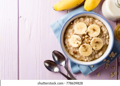 Oatmeal porridge with banana, walnuts and honey in bowl on purple wooden background. Healthy breakfast. Top view. Copy space.
