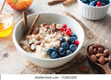 Oatmeal porridge with blueberries, almonds, cinnamon, honey, linseed and red currants in bowl. Super food for healthy nutritious breakfast