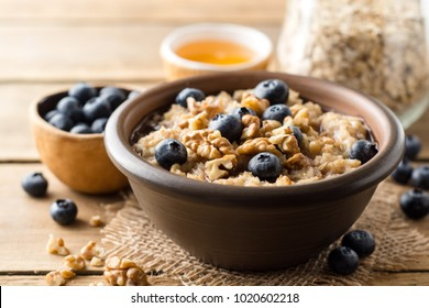 Oatmeal porridge with blueberries, walnuts and honey in ceramic bowl on wooden background. Rustic style. Selective focus.