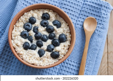 Oatmeal porridge with blueberries and wooden spoon on a blue towel, tasty healthy summer breakfast