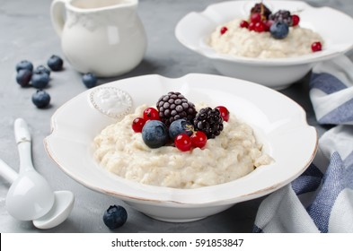 Oatmeal porridge with blueberry, blackberries and currants for breakfast