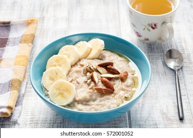 Oatmeal porridge bowl with banana, sliced almonds, sunflower seeds and honey. Healthy nutritious breakfast with cup of green tea
