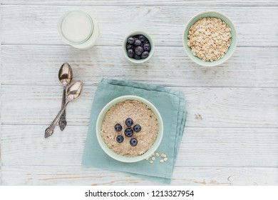 Oatmeal porridge bowl with berry and fruit jam on the white wooden background. Healthy nutritious breakfast. Concept of healthy eating, dieting. Above