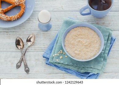 Oatmeal porridge bowl with black tea, bread and boiled egg on the white wooden background. Healthy nutritious breakfast. Concept of healthy eating, dieting. top view