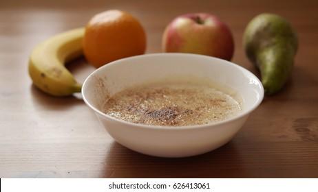 Oatmeal porridge with cinnamon in white bowl and  fresh banana, apple, orange, apple on wooden table