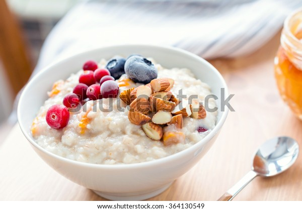Oatmeal porridge with dried apricots, blueberries, cranberries and chopped almonds on bright wooden table. Jar of honey on background. Selective focus. Bright healthy breakfast image
