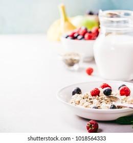 Oatmeal porridge with fresh berries, fruits and almond milk. Healthy breakfast, healthy eating, vegan food concept.