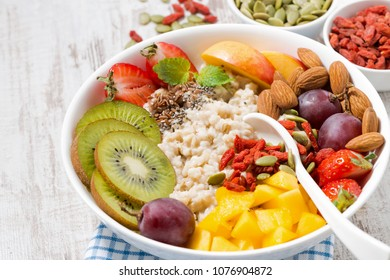 oatmeal porridge with fresh fruits and superfoods on a white wooden background, closeup, horizontal