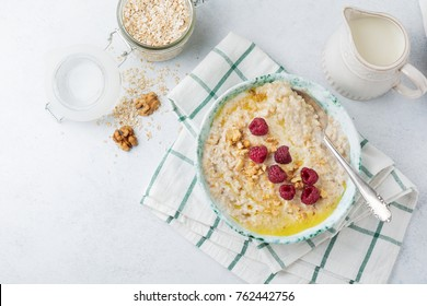 Oatmeal porridge with fresh raspberries, walnuts and butter in a ceramic plate on a light stone or concrete background. Selective focus.