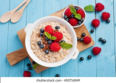 Oatmeal porridge with fresh raspberry and blueberry on bright blue background. Healthy breakfast for children and parents. Tasty vegetarian food.