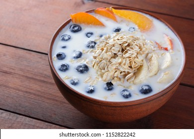 Oatmeal porridge with milk and fruit on wooden background, healthy porridge with pieces of banana and peach, breakfast with fiber, calcium and vitamins