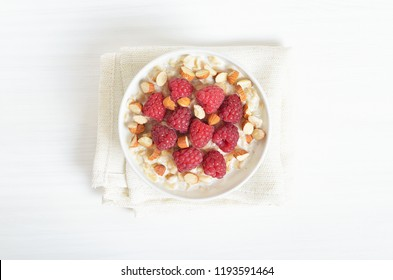 Oatmeal porridge with raspberries and nuts in bowl on white table, top view
