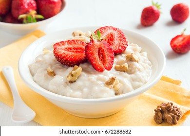 Oatmeal Porridge with Strawberries and Walnuts in white bowl. Healthy Breakfast with Oatmeal and Fresh Organic Berries.