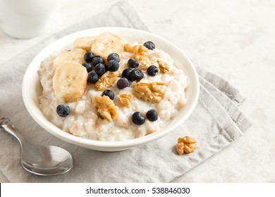 Oatmeal porridge with walnuts, blueberries and banana in bowl  - healthy rustic breakfast